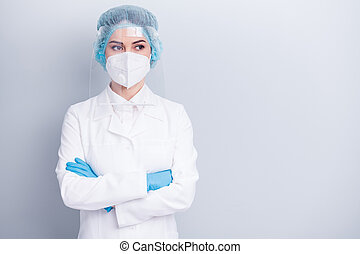 Photo of self-confident virologist doctor lady arms crossed professional watch side intern work wear medical coat mask facial plastic protection shield surgical cap isolated grey background