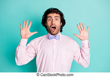 Photo of shocked frightened curly hair man dressed pink shirt two arms up isolated turquoise color background