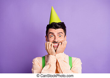 Photo of shocked terrified young man dressed yellow shirt birthday headwear biting two hands arms isolated purple color background