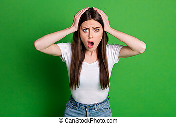 Photo of shocked woman dressed casual outfit arms head open mouth isolated green color background