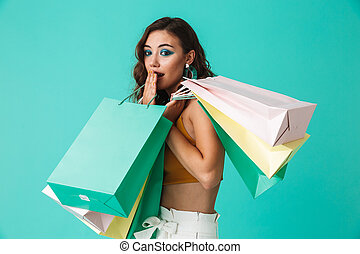 Photo of shopaholic girl 20s wearing fashion style holding colorful paper shopping bags with purchases, isolated over blue background