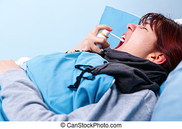 Photo of sick brunette using throat spray lying in bed