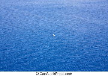 Single boat sailing in a vast ocean - Photo of Single boat...