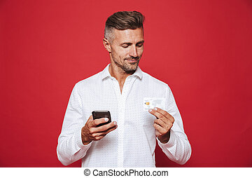 Photo of smiling man in white shirt holding credit card and smartphone, isolated over red background