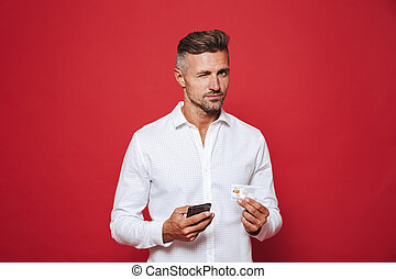 Photo of successful man in white shirt holding credit card and smartphone, isolated over red background
