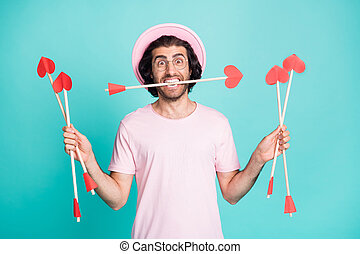 Photo of surprised hipster man hold arrows wear pink cap spectacles t-shirt isolated on teal color background