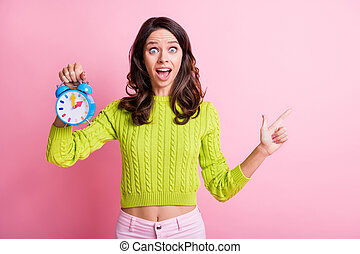 Photo of surprised lady open mouth hold alarm clock indicate finger empty space wear green sweater isolated pink color background
