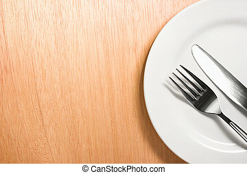 fork and knife with white plate on wooden background