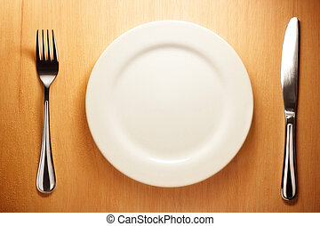 Photo of the fork and knife with white plate on wood