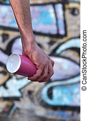 Photo of the hand of a street artist who draws a new color picture on a brick wall