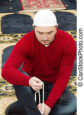 Young muslim man showing Islamic prayer