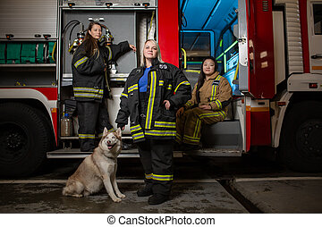Photo of three women firefighters and dog on background of fire truck