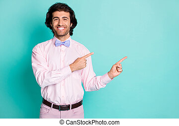 Photo of toothy beaming gentle man wear pink outfit pointing two fingers empty space isolated turquoise color background