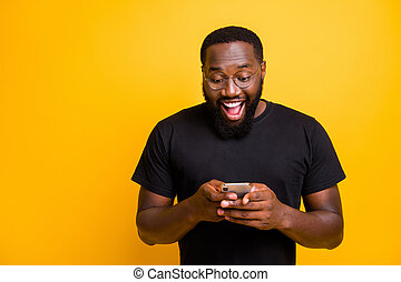 Photo of toothy mixed-race handsome funny man brunet haired in t-shirt overjoyed about receiving positive notification of feedback isolated vivid yellow color background