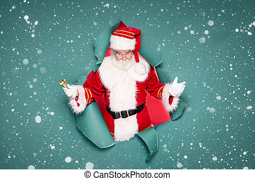Photo of traditional Santa Claus ringing on a gold bell.
