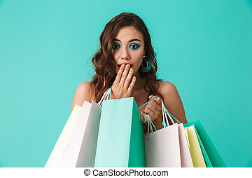 Photo of trendy young girl 20s wearing fashion style holding colorful paper shopping bags with purchases, isolated over blue background