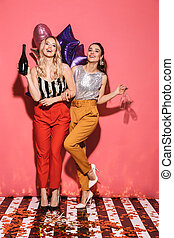 Photo of two european women 20s in stylish outfit holding festive balloons and drinking champagne on party