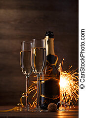 Photo of two glasses with wine, bottles, cork, burning Bengal fire