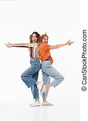 Photo of two joyful girls wearing colorful clothes standing back to back and doing gun gesture with fingers