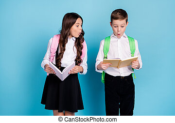 Photo of two little girl boy schoolchildren brother sister classmates hold textbook read unexpected information shocked wear bag white shirt black pants dress isolated blue color background