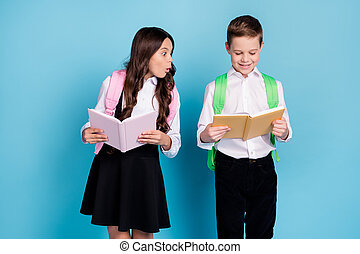 Photo of two little girl boy schoolchildren brother sister classmates hold textbook unexpected unbelievable high grade wear bag white shirt black pants dress isolated blue color background