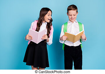 Photo of two little girl boy schoolkid brother sister classmates hold textbook want find out copy homework wear bag white shirt black pants dress isolated blue color background