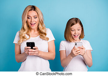 Photo of two people beautiful mom lady little daughter excited mood spend leisure together hold telephones reading post bloggers wear casual white s-shirts isolated blue color background