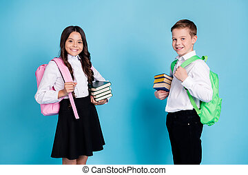 Photo of two small girl boy schoolchildren brother sister classmates hold pile books library study year beginning wear rucksack white shirt black pants dress isolated blue color background