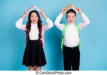 Photo of two small girl boy schoolchildren brother sister classmates hold textbook above head having fun school break wear bag white shirt black pants dress isolated blue color background