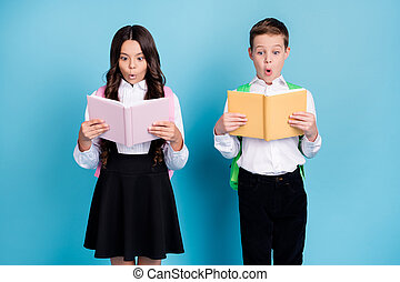 Photo of two small girl boy schoolkid best friends classmates amazed read new hard math paragraph wear backpack white shirt black pants dress isolated blue color background