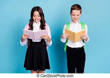 Photo of two small girl boy schoolkid best friends classmates read fine fiction book after school wear backpack white shirt black pants dress isolated blue color background