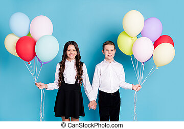 Photo of two small girl boy schoolkid best friends hold hands balloons first school day meet teacher wear white shirt black pants dress isolated blue color background