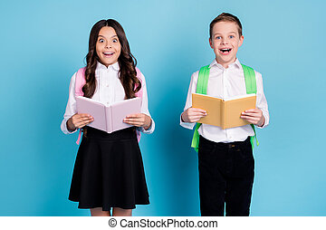 Photo of two small girl boy schoolkid best friends hold textbooks amazed learn new country geographic lesson wear bag white shirt black pants dress isolated blue color background