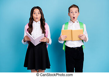 Photo of two small girl boy schoolkids classmates hold copybook open mouth shock read incredible history facts wear bag white shirt black pants dress isolated blue color background