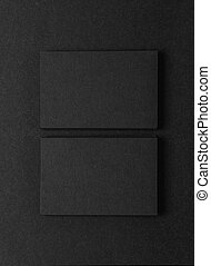 Photo of two stack Of blank black business cards on textile background. Vertical