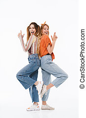 Photo of two teen girls wearing colorful clothes standing back to back and doing gun gesture with fingers
