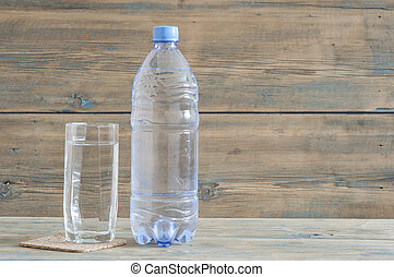 photo of water bottle with glass on wooden table
