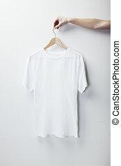 Photo of white tshirt hanging female hand. Vertical