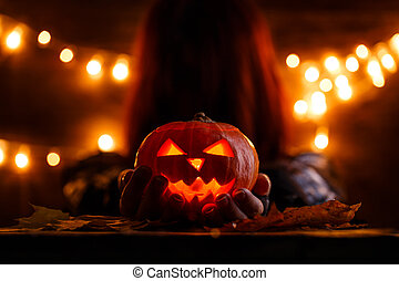 Photo of witch with long hair holding halloween pumpkin