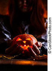 Photo of witch with long hair holding pumpkin