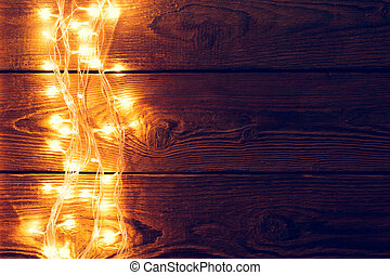 Photo of wooden surface with burning garland on side. Empty...