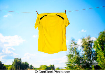 Photo of yellow T-shirt hanging on rope against blue sky background