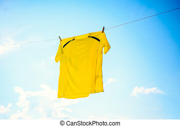 Photo of yellow T-shirt hanging on rope against blue sky
