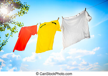 Photo of yellow, white and orange T-shirt hanging on rope against blue sky background with treetops.