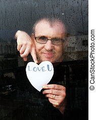 photo of young adult man standing at the window on a rainy day with paper heart
