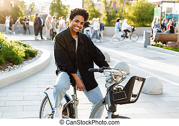Photo of young african american woman smiling while sitting on bicycle in city park