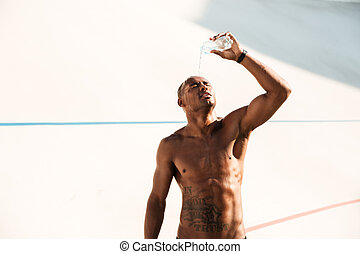 Photo of young african sports man pouring out water on his head