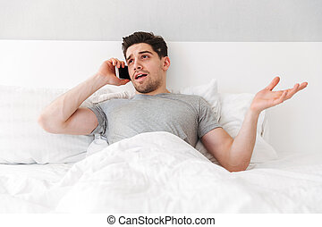 Photo of young caucasian man lying alone in bed with white linen, and having important mobile call