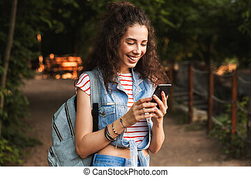 Photo of young delighted woman 18-20 with backpack, smiling and looking at smartphone in hand while standing on path in green park