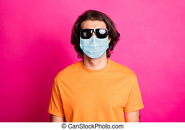 Photo of young man look camera wear medical mask orange t-shirt sunglass isolated pink color background